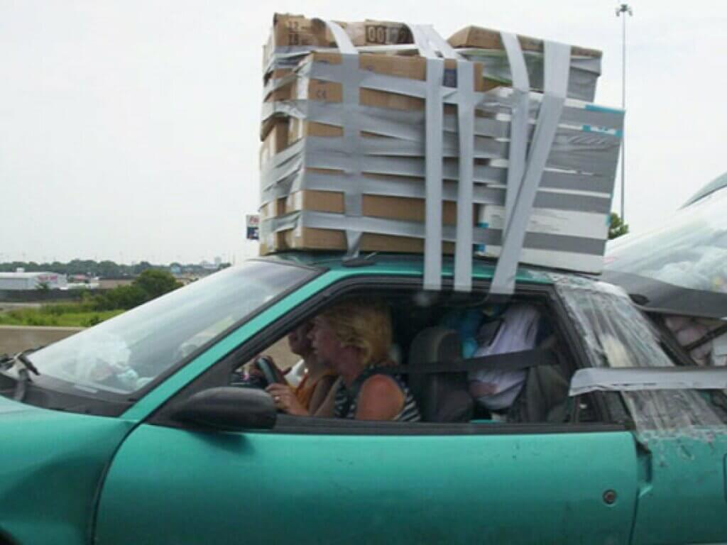 a hatchback car with duct tape holding all the boxes on the roof