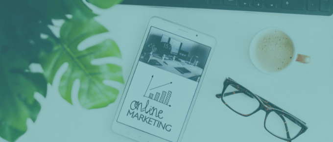 A picture of a phone on a desk that says online marketing along with a coffee cup and a big green leaf of a plant.